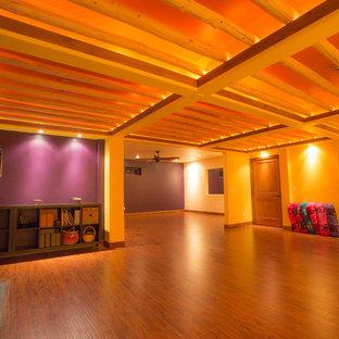 Großer Rustikaler Yogaraum mit lila Wandfarbe, braunem Holzboden und braunem Boden in Denver