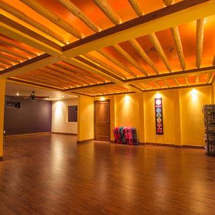Immagine di un grande studio yoga stile rurale con pareti viola, pavimento in legno massello medio e pavimento marrone