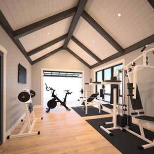 Cette photo montre une grand salle de musculation tendance avec un mur gris et un sol en bois clair.