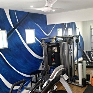 Example of a mid-sized minimalist light wood floor home weight room design in Los Angeles with multicolored walls