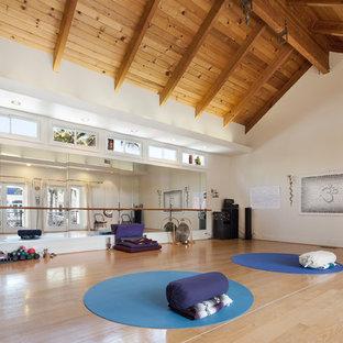 Multifunktionaler Mediterraner Fitnessraum mit weißer Wandfarbe, hellem Holzboden und braunem Boden in Los Angeles