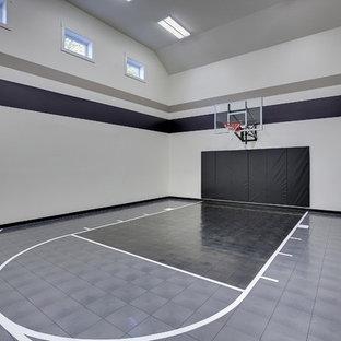 Immagine di un ampio campo sportivo coperto classico con pareti grigie, pavimento in vinile e pavimento grigio