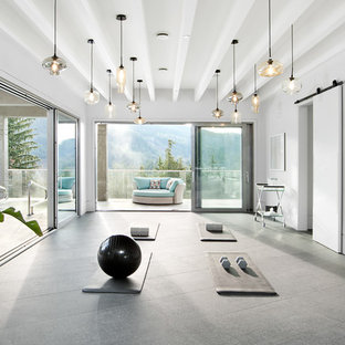 Contemporary home yoga studio in Vancouver with white walls and grey floors.