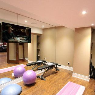Foto di uno studio yoga tradizionale di medie dimensioni con pareti beige, pavimento in laminato e pavimento marrone