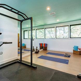 Immagine di un grande studio yoga classico con pareti blu, pavimento in legno massello medio e pavimento beige