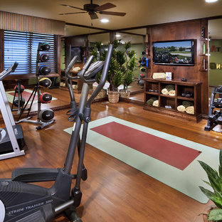 Example of a tuscan medium tone wood floor and brown floor home gym design in Denver with green walls