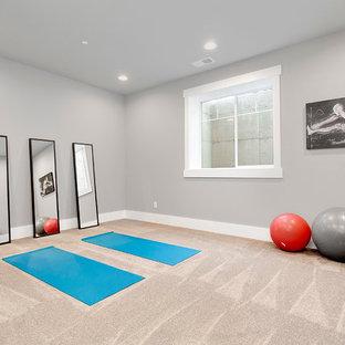 Immagine di un grande studio yoga tradizionale con pareti grigie, moquette e pavimento beige