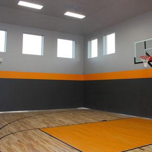 Esempio di un grande campo sportivo coperto american style con pareti grigie e pavimento in legno massello medio