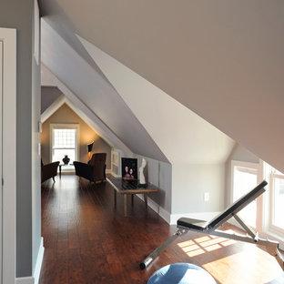 Foto di una sala pesi moderna di medie dimensioni con pareti grigie e pavimento in legno massello medio