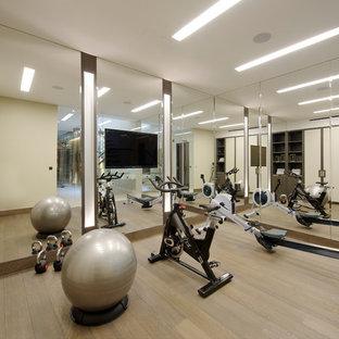 Immagine di una palestra multiuso design di medie dimensioni con pareti beige, pavimento in legno massello medio, pavimento marrone e soffitto a cassettoni