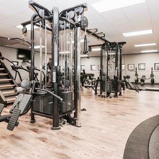 Свежая идея для дизайна: большой универсальный домашний тренажерный зал в современном стиле с серыми стенами, полом из ламината и коричневым полом - отличное фото интерьера