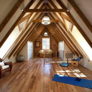 Diseño de estudio de yoga tradicional renovado, grande, con paredes blancas y suelo de madera en tonos medios