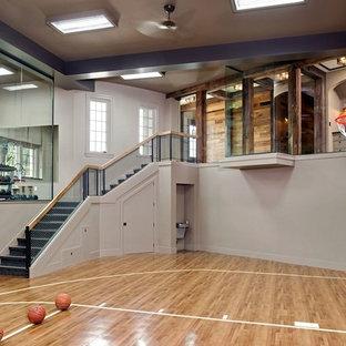 Foto di un campo sportivo coperto classico con pareti grigie, pavimento in legno massello medio e pavimento beige