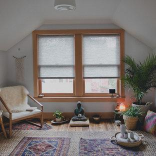Inredning av ett klassiskt mellanstort hemmagym med yogastudio, med vita väggar och ljust trägolv