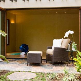 Idee per uno studio yoga tropicale di medie dimensioni con pareti beige, parquet chiaro e pavimento beige