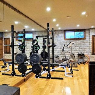 Esempio di una sala pesi stile rurale di medie dimensioni con pareti grigie, parquet chiaro e pavimento beige