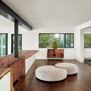 Idee per uno studio yoga minimalista di medie dimensioni con pareti bianche, parquet scuro e pavimento marrone