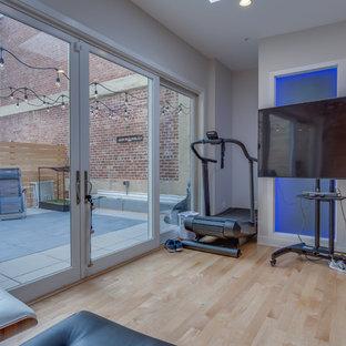 Immagine di una piccola sala pesi minimalista con pareti bianche, parquet chiaro e pavimento beige