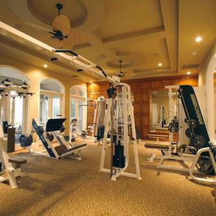 Immagine di una grande sala pesi classica con pareti beige e moquette