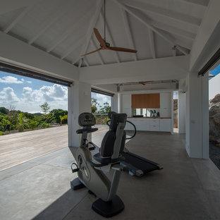 Multifunktionaler Tropenstil Fitnessraum mit weißer Wandfarbe und Betonboden in Sonstige