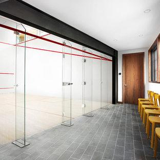 Immagine di un ampio campo sportivo coperto minimalista con pareti bianche, pavimento in laminato e pavimento marrone