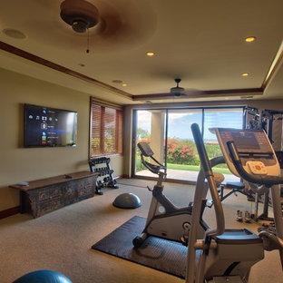 Immagine di una grande sala pesi tropicale con pareti beige, moquette e pavimento beige