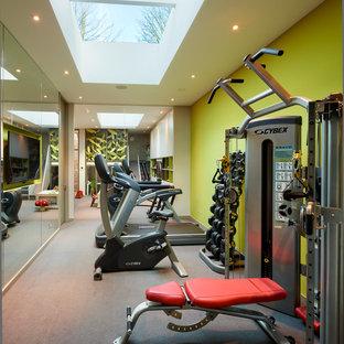 Multifunktionaler Moderner Fitnessraum mit grüner Wandfarbe und grauem Boden in London