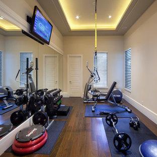 Idee per una sala pesi classica con pareti beige, parquet scuro e pavimento marrone