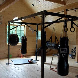 Ispirazione per una grande sala pesi stile rurale con pareti marroni e pavimento in legno massello medio