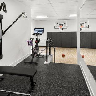 Immagine di un grande campo sportivo coperto minimalista con pareti bianche, pavimento in laminato e pavimento marrone