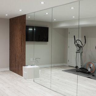 Esempio di una grande sala pesi minimalista con pareti grigie, pavimento in laminato e pavimento grigio
