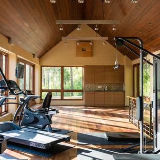 Ispirazione per una sala pesi design con pareti beige e pavimento in legno massello medio
