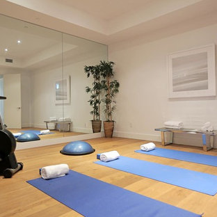 Mid-sized minimalist medium tone wood floor home yoga studio photo in Los Angeles with white walls