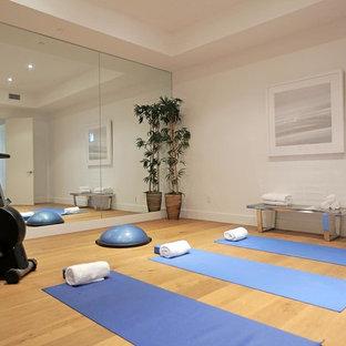Diseño de estudio de yoga minimalista, de tamaño medio, con paredes blancas y suelo de madera en tonos medios