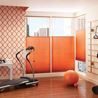 Immagine di una palestra multiuso minimalista di medie dimensioni con pareti beige e pavimento in legno massello medio