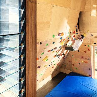 Moderner Fitnessraum mit Kletterwand, brauner Wandfarbe und braunem Boden in Brisbane