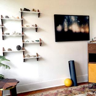Foto di una piccola palestra in casa minimal con pareti bianche, pavimento in legno massello medio e pavimento marrone