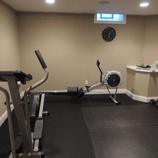 Immagine di una sala pesi chic di medie dimensioni con pareti beige, pavimento in vinile e pavimento nero