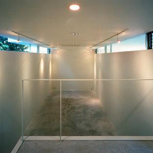 Idee per un atelier moderno di medie dimensioni con pareti bianche, pavimento in cemento, nessun camino, scrivania incassata, pavimento grigio e cornice del camino in cemento
