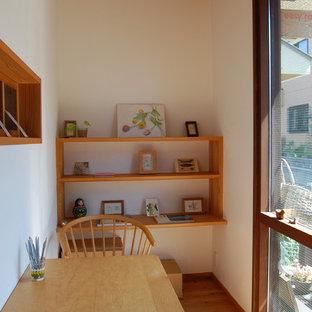 Foto di un piccolo studio etnico con pareti bianche, parquet chiaro, scrivania autoportante e nessun camino