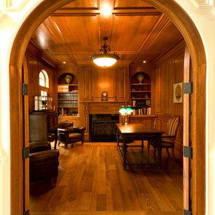 ボストンの大きいトラディショナルスタイルのおしゃれなホームオフィス・仕事部屋 (ライブラリー、茶色い壁、濃色無垢フローリング、標準型暖炉、木材の暖炉まわり、自立型机、茶色い床) の写真