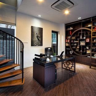 Immagine di uno studio etnico con pareti bianche, parquet scuro e scrivania autoportante