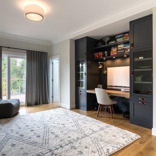 サンフランシスコの広いトランジショナルスタイルのおしゃれな書斎 (白い壁、無垢フローリング、造り付け机、茶色い床、暖炉なし) の写真