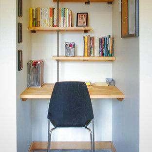 他の地域の小さいコンテンポラリースタイルのおしゃれなホームオフィス・書斎 (白い壁、コンクリートの床、造り付け机) の写真