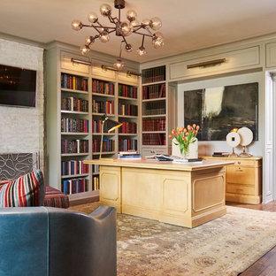 Modelo de despacho clásico con paredes verdes, suelo de madera en tonos medios, todas las chimeneas, marco de chimenea de piedra, escritorio independiente y suelo marrón