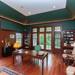 Immagine di un grande studio classico con libreria, pareti verdi, pavimento in legno massello medio, scrivania autoportante e pavimento multicolore