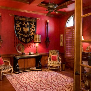 Mittelgroßes Klassisches Arbeitszimmer ohne Kamin mit Arbeitsplatz, roter Wandfarbe, dunklem Holzboden und freistehendem Schreibtisch in Charleston