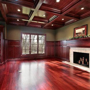 Klassisk inredning av ett stort arbetsrum, med ett bibliotek, gröna väggar, mörkt trägolv, en standard öppen spis och en spiselkrans i trä