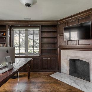 Immagine di uno studio tradizionale di medie dimensioni con libreria, pareti marroni, pavimento in legno massello medio, cornice del camino in pietra e scrivania autoportante