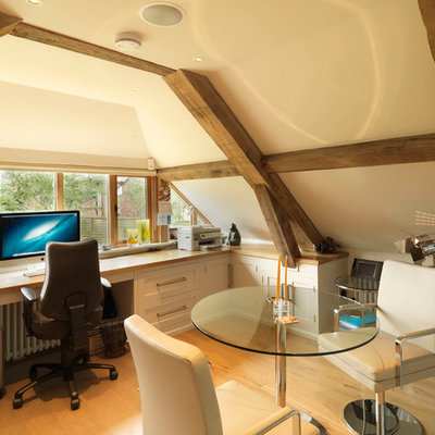 Study room - large country built-in desk medium tone wood floor study room idea in Hampshire with beige walls